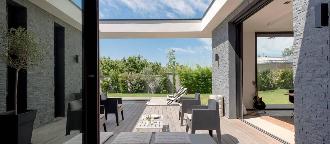 Parfaitement intégré à l'architecture le patio à ciel ouvert s'illustre comme un trait d'union entre la cuisine, le salon et la piscine. Revêtue de teck, la terrasse réchauffe l'atmosphère minérale omniprésente. Fauteuils Toy, de Philippe Starck pour Driade. Banquette et transats AM.PM.