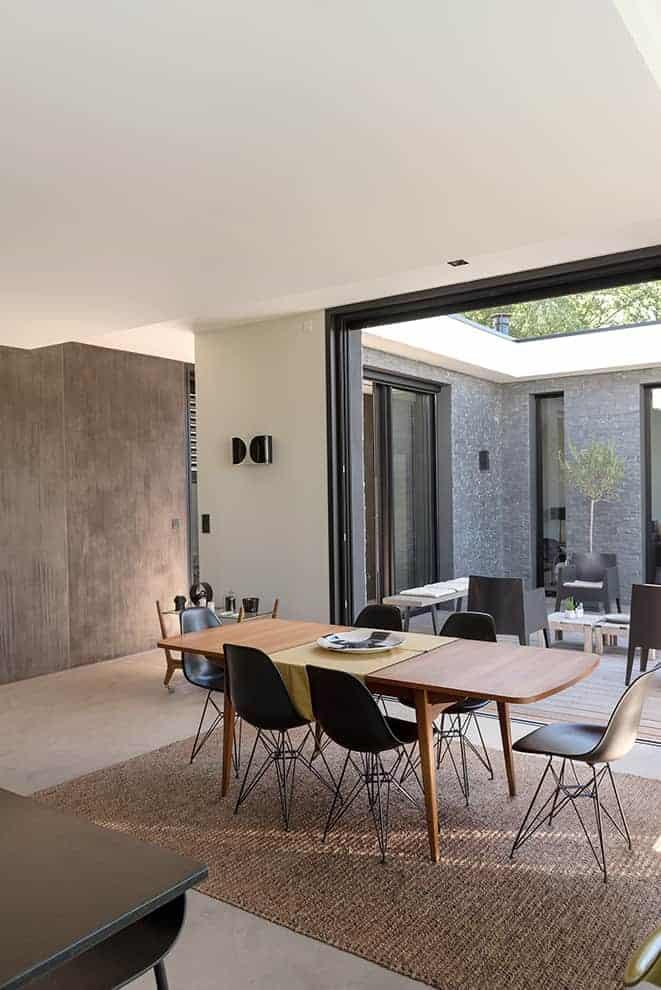 Entièrement ouverte sur le patio, grâce à la baie à galandage Technal, la salle à manger démultiplie sa surface en période estivale. Table de famille, en teck. Applique Foglio, de Flos. Tapis sisal.