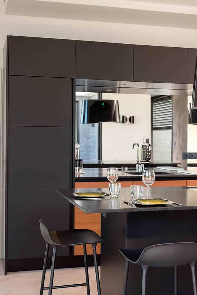 La cuisine Cesar, réalisée par Show Home Concept, reprend le duo noir et bois, ici matérialisé par des façades en Fénix® et en teck. La crédence en miroir permet d'augmenter la luminosité et de créer des perspectives avec l'architecture.