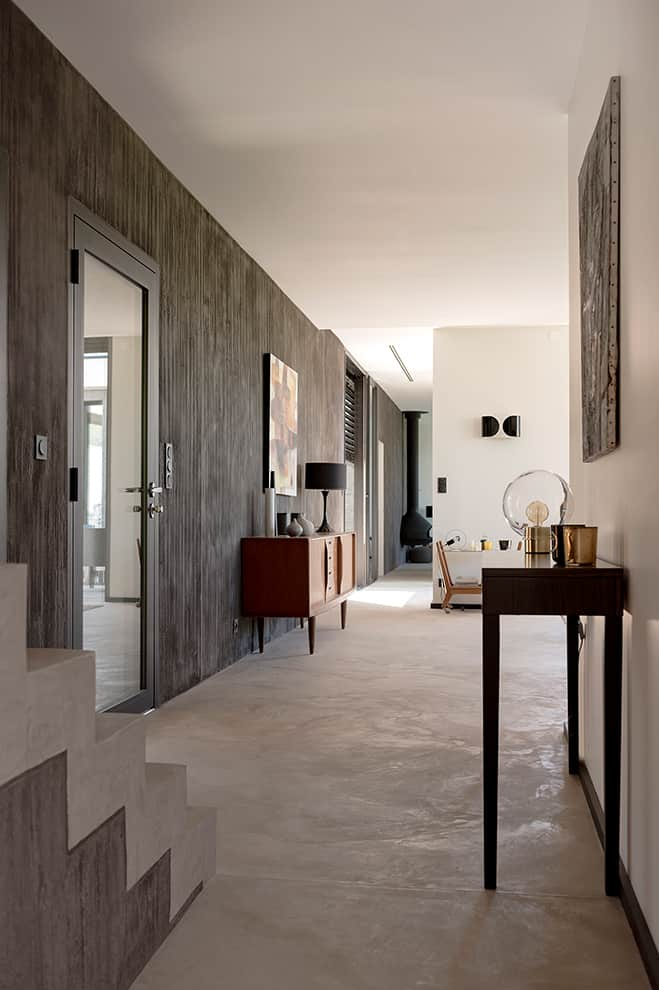 L'entrée pose le décor. Cette notion de clair-obscur transparaît aux murs avec l'enduit matiéré noir carbone aux empreintes verticales qui suivent le mur de 17 mètres de longueur. Au sol, le béton presque blanc flatte les volumes et la lumière naturelle.