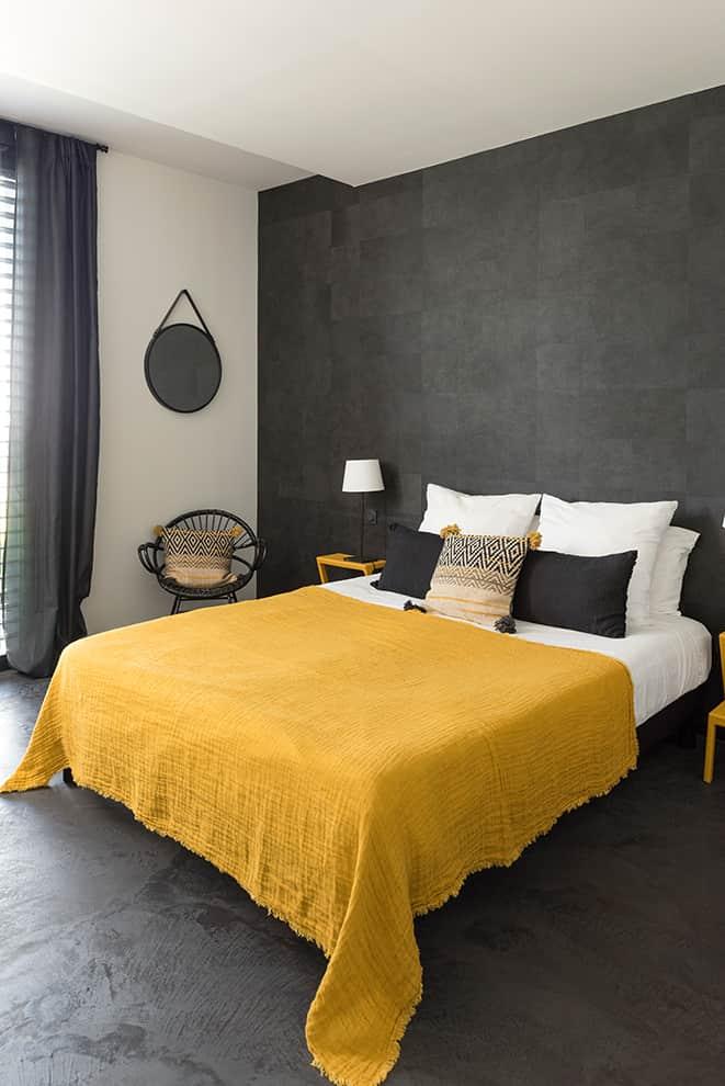 La chambre, située au nord, prend le parti du noir, avec le papier peint Élitis et le béton coloris carbone.