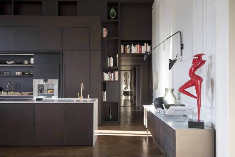 Cuisine avec meuble bibliothèque comprenant des portes pliantes rentrantes. Réalisation Modulis (Lyon 6ème).
