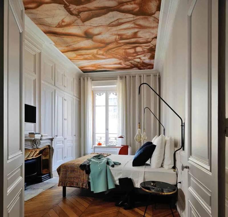 Au plafond, le papier peint illustre une sanguine du peintre Pierre Puvis de Chavannes. Appliques murales réalisées sur-mesure. Bureau du designer Mark Held et chaise de Panton, Vitra.