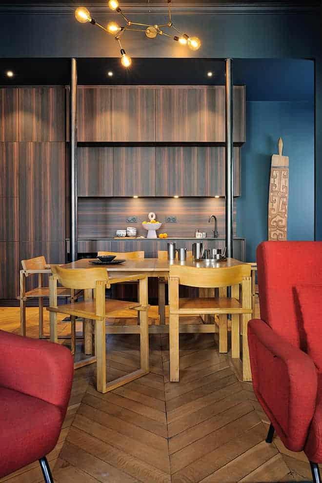 Cuisine dessinée par l'architecte Marie-Anne Chapel et réalisée par la menuiserie ABM, en stratifié structuré finition pin brûlé. À ses côtés, l'espace salle à manger fait le lien avec le salon, via une composition de table et de cabriolets scandinaves, des années 60. Au plafond, le luminaire en laiton a été créé par un artisan grenoblois.