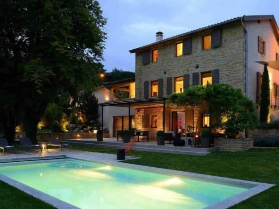 Vue de la maison en pierres dorées sur 3 niveaux Terrasse d'été, avec piscine réalisée par Piscine Concept (Lyon 5ème) Réalisation architecture d'intérieur Dorga - David Burles Photographe Erick Saillet