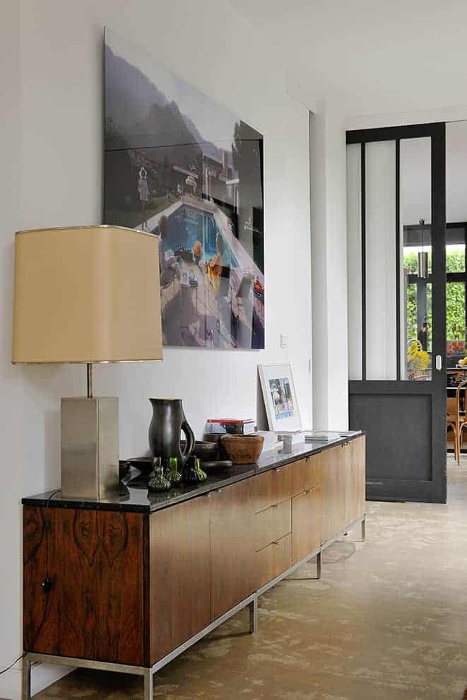 Dans le couloir menant au salon/salle à manger, l'enfilade Knoll, designée par Florence Knoll, en bois de palissandre et marbre noir, chinée aux Puces du Canal, crée le lien.