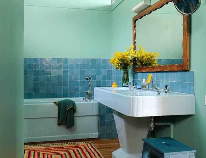 Au même étage, la salle de bains invitée rafraîchit le coin nuit avec ses nuances vert d'eau et bleu ciel.