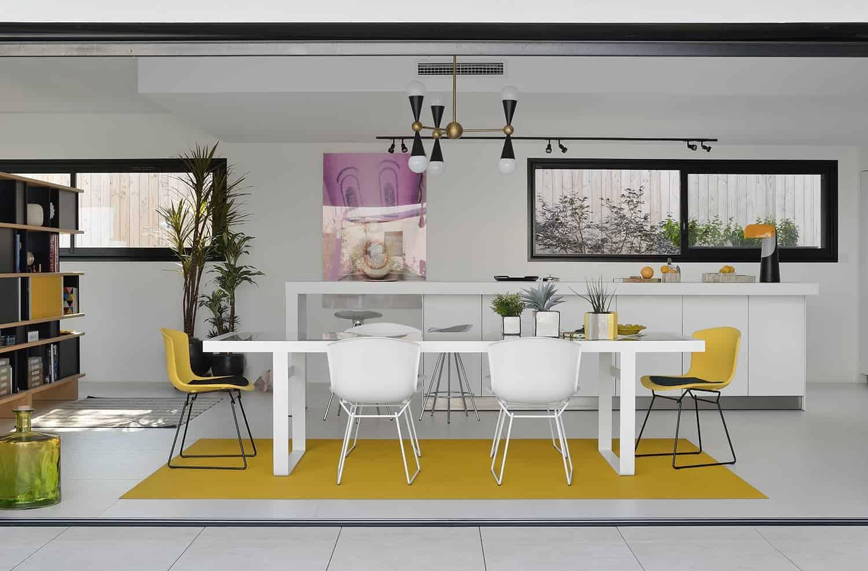 L'espace salle à manger et cuisine, signée Bulthaup Lyon, entièrement tourné vers l'extérieur (baie à galandage de 4,70 mètres de largeur) joue sur la linéarité de l'espace jour, avec un coin-repas identifié par le tapis Bolon, déniché chez IF Contemporain valorisant la table Lens de B&B Italia, imaginée par Patricia Urquiola, dénichée chez Création Contemporaine, à l'instar des chaises Bertoia Molded Shell Side Chair, de 1960. Au-dessus, la pièce marquante : la suspension Caracas de Jonathan Adler, designers aux inspirations Mid-Century marquantes. En toile de fond, une photographie de l'artiste Philippe Shangti. L'ensemble valorisé par l'aplat blanc, le grès cérame Touché d'Inalco, choisi chez Espace Crozet.