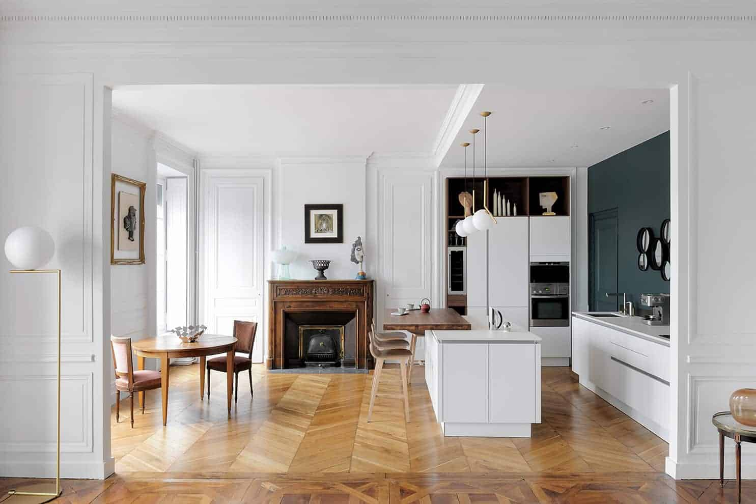 Espace cuisine/salle à manger. Parquet chevron d'origine. Cheminée en noyer d'époque. Cuisine contemporaine Nolte, réalisée par EC Cuisines. Tables et chaises de famille.