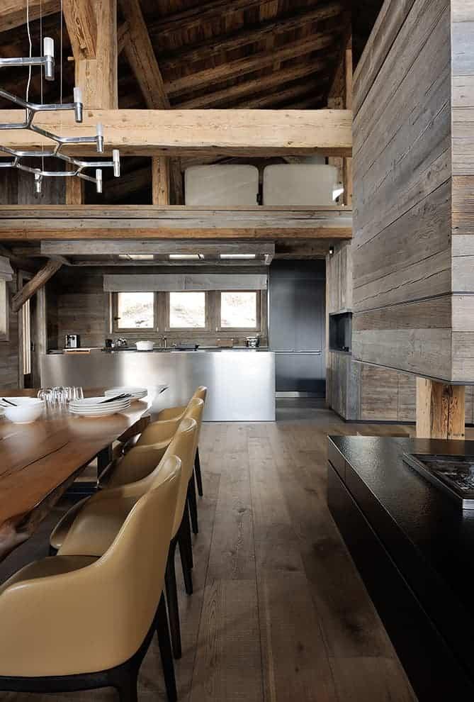 Face à la salle à manger, la cuisine ouverte met en valeur l'îlot monolithique en inox, réalisé sur-mesure par Bulthaup Lyon. En résonance, le bloc hotte disparaît derrière un cadre bois. En premier plan, on remarque la finesse d'intégration, des joints creux métalliques, que l'on retrouve sur les panneautages bois, dans l'ensemble du chalet