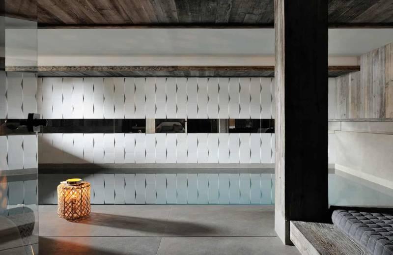 L'espace wellness, digne de ce nom, évolue non pas en sous-sol, mais entre le rez-de-neige et le salon. Au carrelage mural cintré s'ajoute une ligne miroir dans l'alignement de la niche rétroéclairée, maîtrisant ainsi les perspectives. Parement céramique en 3D, Wou. Sol en céramique Casa Dolce Casa.