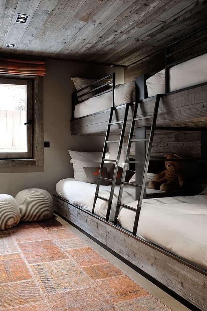Dessiné sur-mesure par les architectes d'intérieur, le dortoir, en rez-de-neige, présente la particularité ingénieuse : des lits de 120 cm surmontés de lits de 90 cm. Une astuce qui permet de lire une histoire sans avoir à se recroqueviller ! Chaque lit intègre une liseuse et une niche rétroéclairée. Amovibles, les échelles peuvent aisément se retirer. Tapis Gan-Rugs. Poufs Casalis.