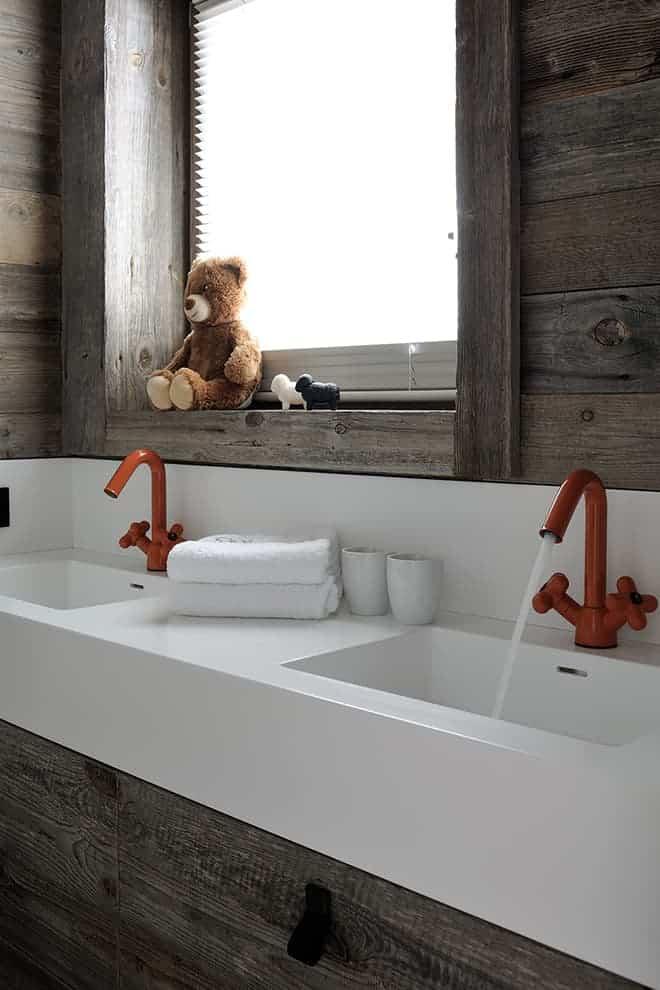 La salle de bains attenante met en exergue la robinetterie ludique Fantini, qui a insufflé le thème chromatique à la chambre. Double vasque en Corian®, réalisée sur-mesure.