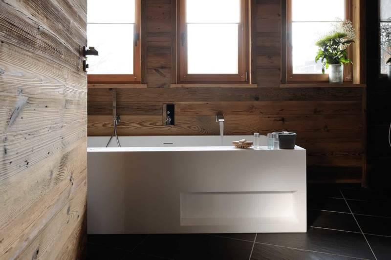 La salle de bains, réalisée par Espace Crozet, reprend la dimension contemporaine de la cuisine avec son carrelage en relief et sa baignoire Aquamass. Porte en vieux bois avec poignée choisie chez LBA Thivel.