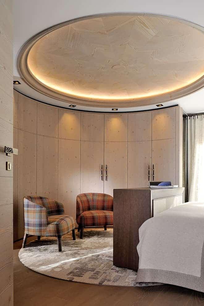 Cette chambre témoigne du travail effectué sur l'agencement, avec son dressing cintré, suivant à la perfection la rosace rétroéclairée en bois. Fauteuils B&B Italia. Tapis Stepevi. Poignées de chez Portes Design.