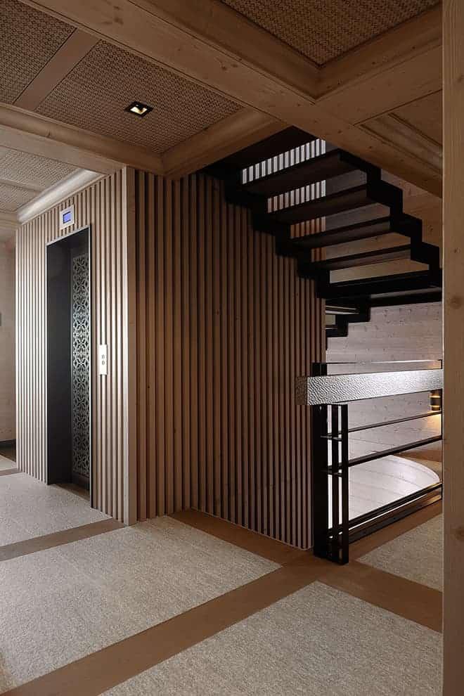La démarche conceptuelle relie tous les espaces du chalet avec une cohérence esthétique que l'on retrouve dans les circulations : le calepinage en damier, l'empreinte du textile, les profils muraux… Même l'ascenseur bénéficie d'une touche décorative, avec une grille en métal dentelé.
