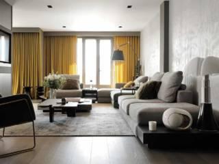 En premier plan : céramiques Fornasetti, table basse dessinée sur-mesure reprenant le revêtement bois de l'agencement. Au second plan : tabourets AM.PM et rideaux en velours confectionnés par HomeMaison.