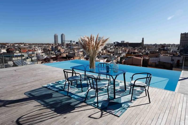 Collection de mobilier outdoor Angel. Bridges en aluminium (58 x P 55 x H 79 cm) et tables en aluminium et verre (213 x 103 x H 75 cm). ©Roche Bobois