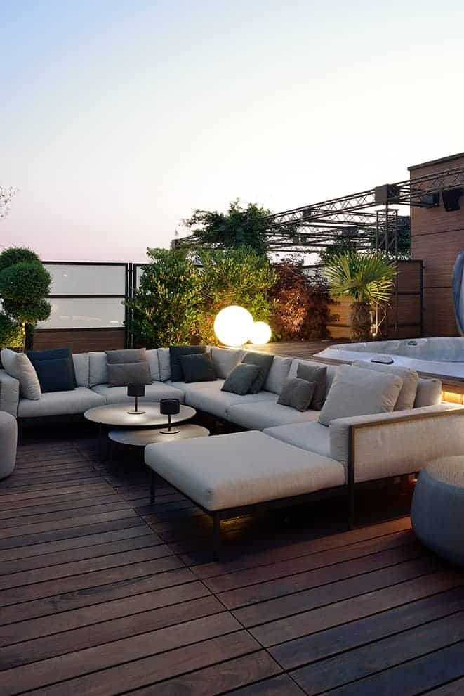 Au nord-est, le coin lounge matérialisé par le système d'assises Natal Alu et les poufs outdoor (Tribù).