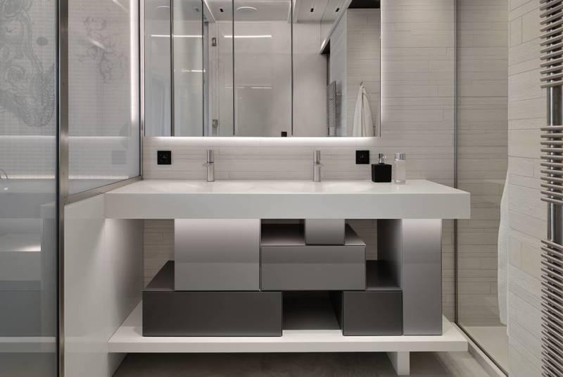 Le dessin tramé omniprésent se retrouve dans la salle de bains, sur le meuble dessiné par l'agence Fleury et le calepinage du carrelage Marazzi.