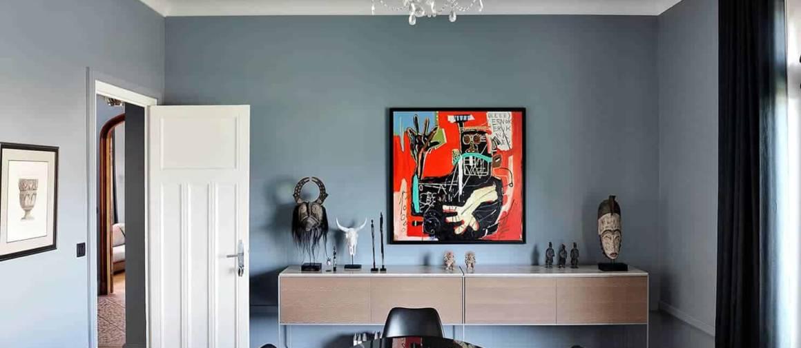 À ses côtés, la salle à manger retrouve une aura plus classique. Rideaux (Bisson Bruneel). Table et chaises Saarinen (Knoll). Console de 3 mètres sur-mesure en placage bois Marotte et plan en marbre Crema Marfil. Au mur, réédition de l'artiste Basquiat chinée chez Sans Contrefaçon.
