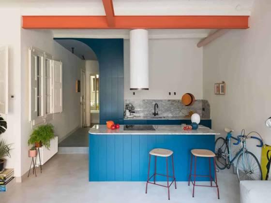 La cuisine, conçue par CaSA et réalisée par Rec Disseny, s'habille d'une boiserie composée de panneaux rainurés laqués dans un bleu profond, adoucis par le marbre incurvé de Portobello sur le plan de travail et la crédence. Hotte Corinthia (Faber). Tabourets Edge 30 (Hay). Au mur, tableaux graphiques Gripface.