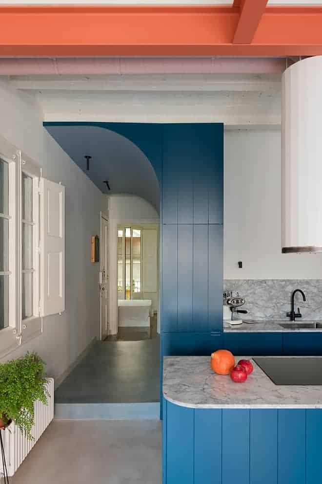 Centre névralgique de la conception, le volume bleu lambrissé, trait d'union entre la partie jour et la partie nuit, dissimule les rangements, les éléments techniques et via des portes escamotables.