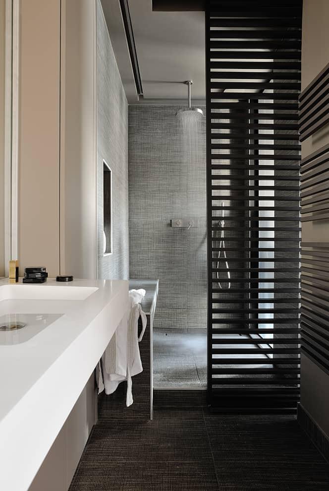 La salle de bains a été entièrement calibrée sur les persiennes. Plan vasque en Corian®, robinetterie et sèche-serviettes, choisis chez Richardson. Carrelage effet tissu chez Décocéram.