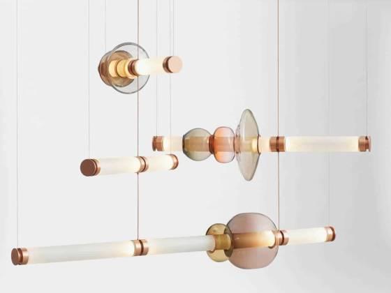 Luna Chandelier – Série de luminaires en verre soufflé, tubes translucides finition lisse et brillante et métal finition cuivre satiné. Modèle Tier 3. L. 146,86 cm. ©Gabriel Scott