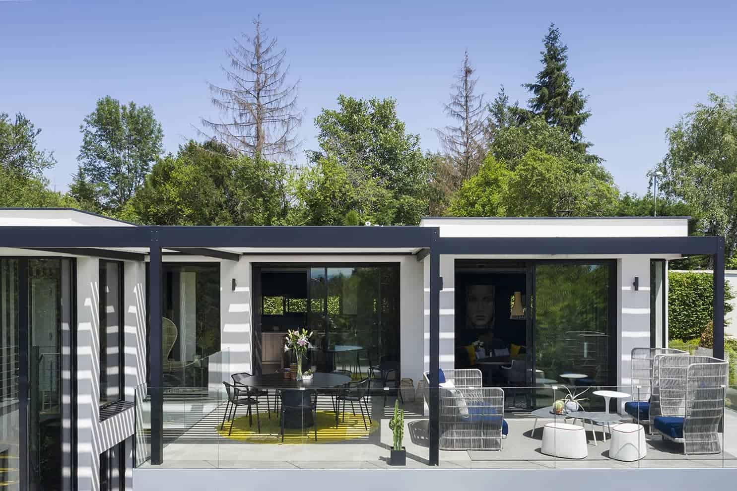 Sur la terrasse panoramique qui borde les pièces de jour et la master suite, la pergola (Solisystème® - Passion Design) recouvre la superficie totale. Grâce à la réinterprétation de Maison Home Design, intérieur et extérieur s'inscrivent dans un clair-obscur, redonnant à chaque zone de vie une présence affirmée.