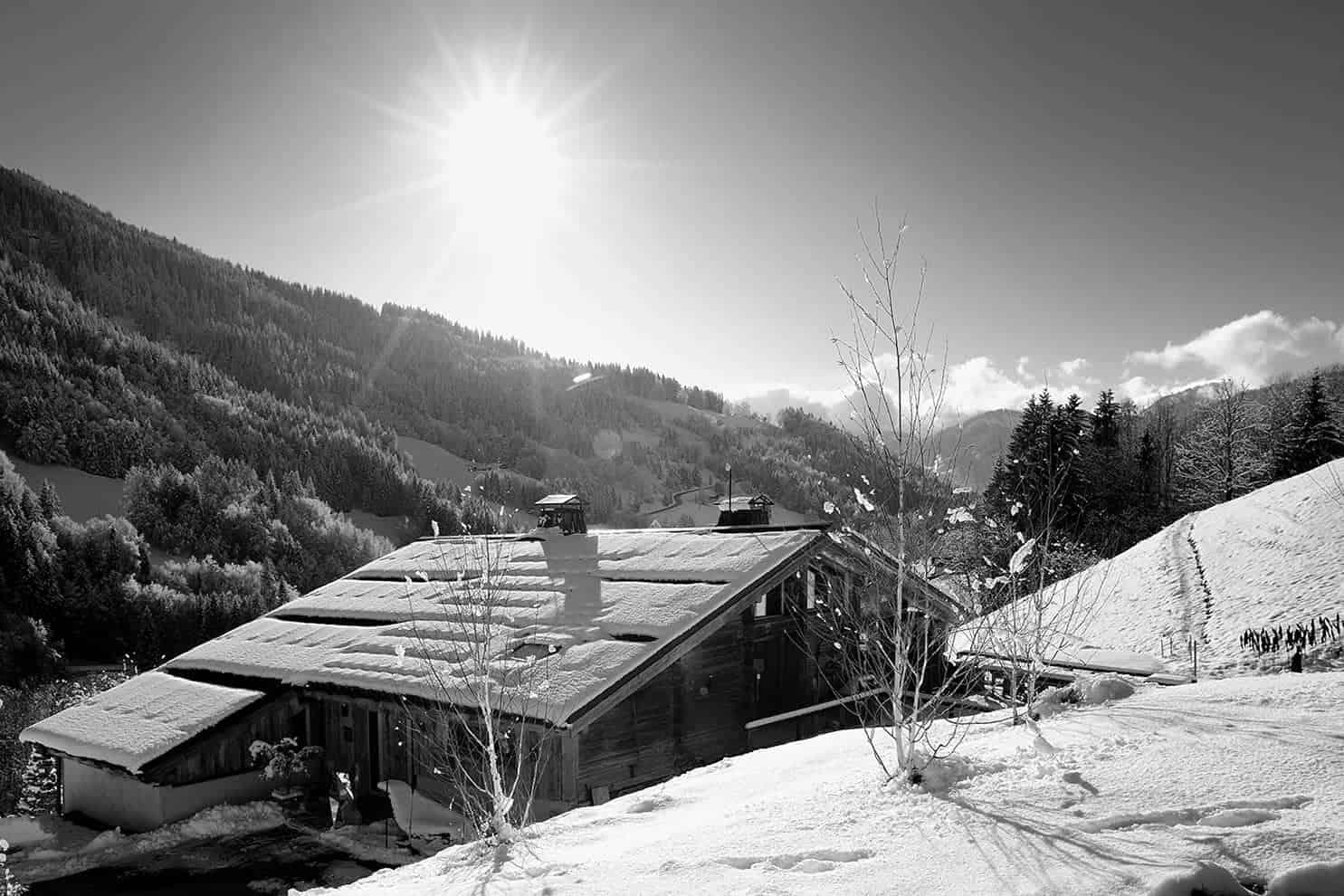 Située à Flumet, au cœur du val d'Arly, cette ferme a conservé toute sa rusticité, préservée par les artisans locaux, ici, véritables orfèvres. Au plus proche du paysage, elle incorpore le dénivelé au sein même de son architecture, appelé le « montagni » (expression locale), contribuant naturellement au déneigement de la toiture.
