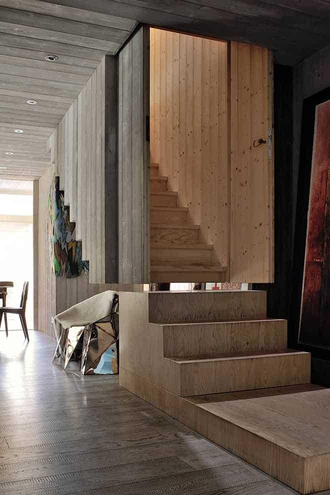 Passion oblige ! Dans cette zone familiale, situé à l'étage inférieur, on retrouve les pièces de la Galerie Armel Soyer, accessible par un escalier contenu dans une boîte suspendue, au dessin contemporain. En arrière-plan, fauteuil Glenda de Julian Mayor.