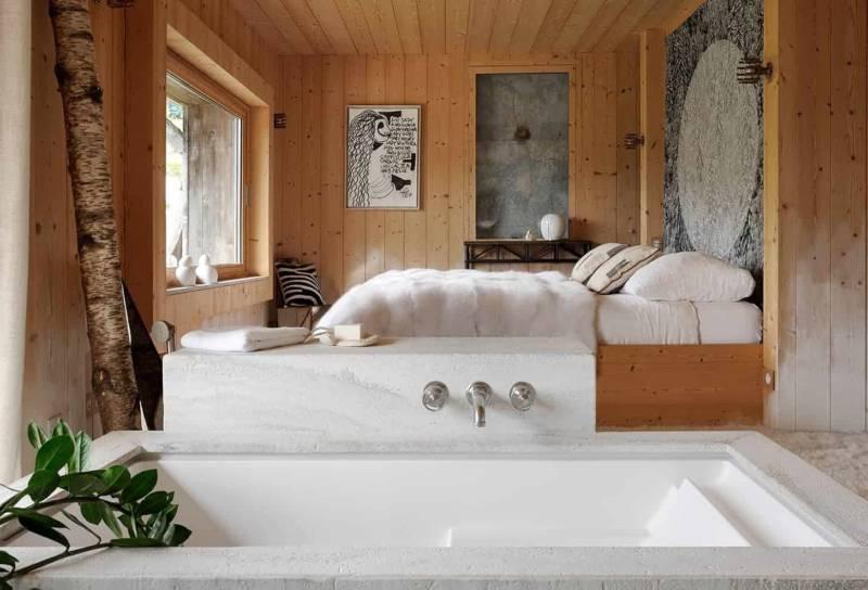 Salle de bains habillée de travertin Muzillac Agrippa fine (Hullebush). Miroir en rotin vintage (Maison Jaune studio), entouré des appliques Sugar Bomb en quartz et cristal de roche de Christopher Boots.