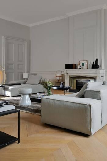 La proportion généreuse des assises s'inscrit également en résonance avec celle de la cheminée en marbre blanc d'origine, au foyer particulièrement large, à l'instar de ses sœurs disséminées de part et d'autre de l'appartement.