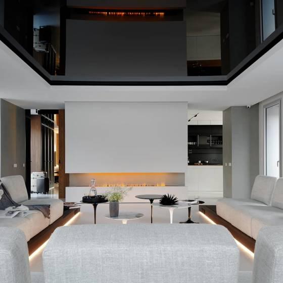 Pièce maîtresse, le salon se distingue par cette composition d'assises modulables, dessinées par les architectes, via le rail périphérique intégré au podium en chêne teinté. Une estrade astucieuse pour mieux créer la continuité avec la terrasse extérieure. Le living fait le lien naturellement avec la master suite et l'espace nuit. Toile tendue laquée noire (Barrisol) Cheminée au gaz (Cheminée Gaudin). Tables d'appoint Saarinen (Knoll chez Arrivetz).