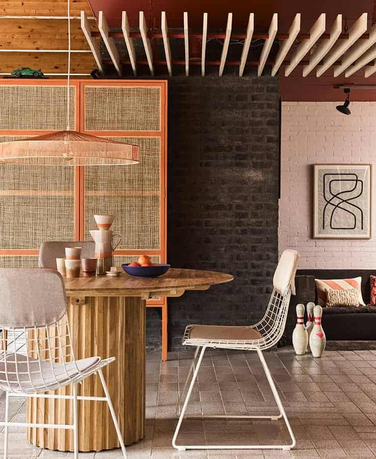 Wire/Pillar/Retro Webbing – Chaise en métal. 47 x 54 x H. 86 cm. Table en teck. Ø 140 x H. 75. Armoire en bois sunkai et poignées en laiton. 125 x 40 x H. 200 cm. ©HK Living