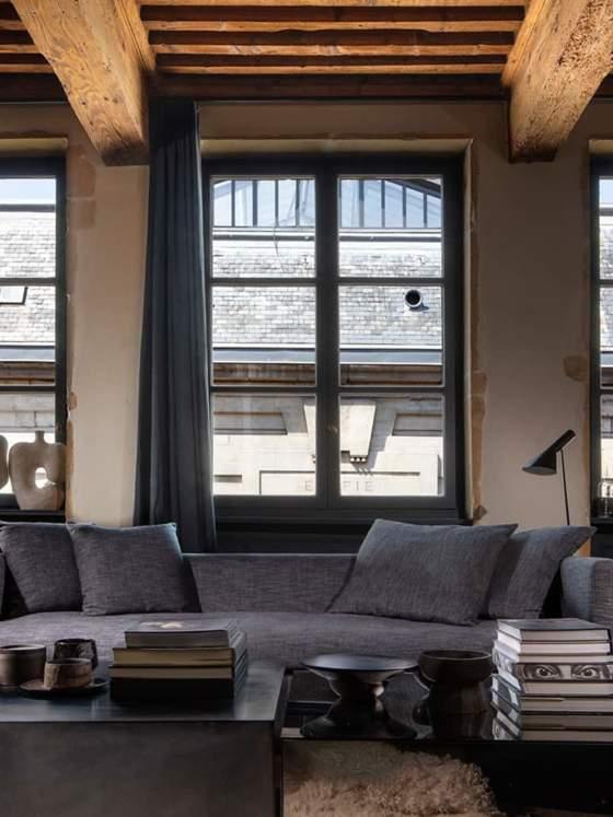 La pièce unique est privilégiée entre canapé dessiné par Maison Hand, meubles et objets chinés. Revêtement tissu et rideaux (Bisson Bruneel)