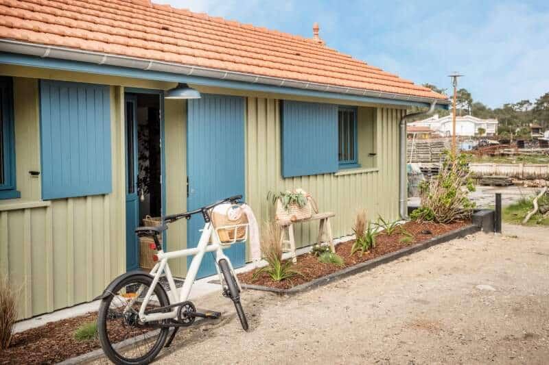 Cabane Yndō, les pieds dans l'eau, aux couleurs du Cap Ferret. Vélo électrique Van Moof