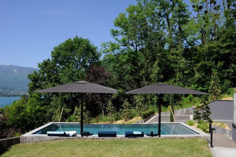 En contrebas la piscine s'aligne sur l'horizon du lac. Parasols et bains de soleil (Kettal)