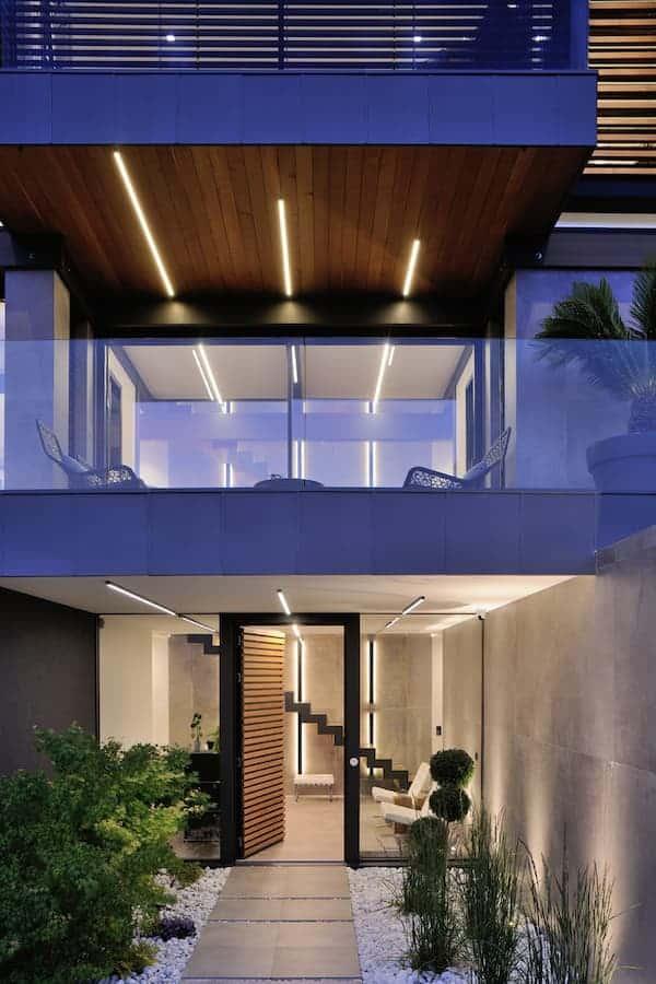 La conception lumière s'exprime dès l'entrée, les profilés alignés sur les étages dialoguant avec l'architecture