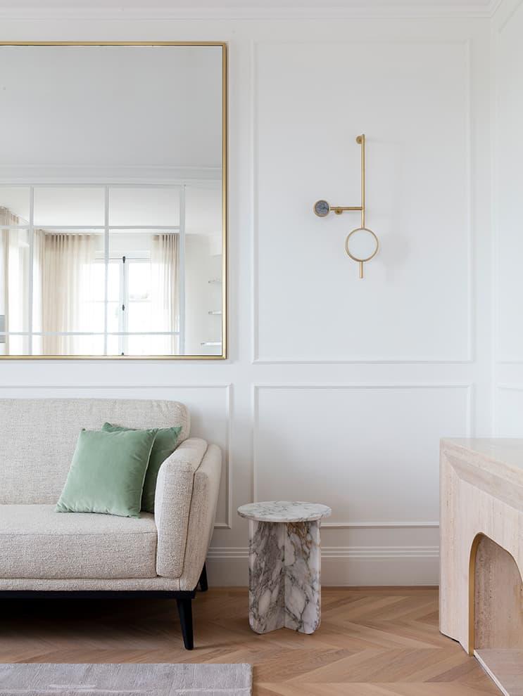 Canapé en tissu Nobilis – table basse en marbre Arabescato, applique en laiton et marbres – Miroir en laiton. Dessinés par Fabien Roque