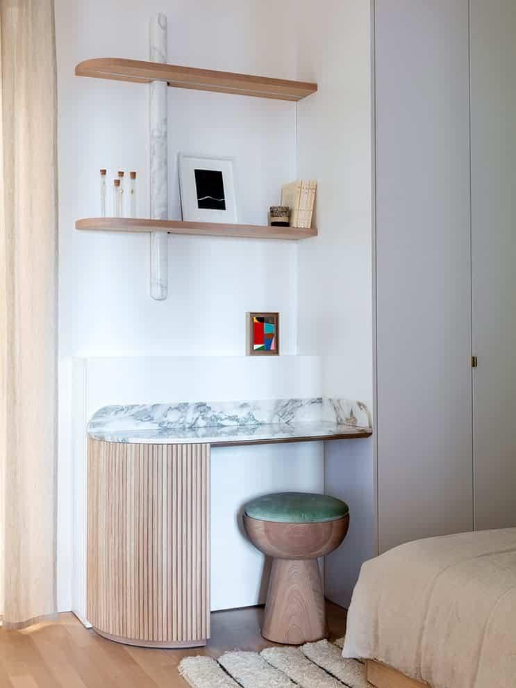 Espace bureau de la chambre d'enfants avec étagères en placage chêne, luminaires traversant en albâtre et bureau en marbre Arabescato et chêne cannelé