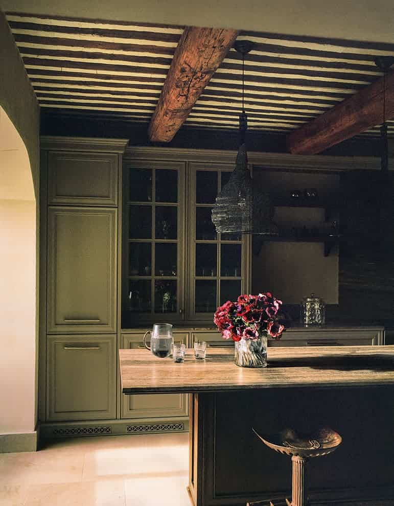 Espace cuisine avec meubles à corniches, moulures et plateau en travertin bronze