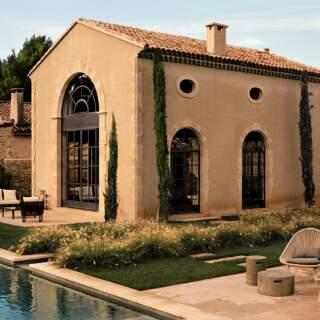 Façade La Bastide de Fléchon. Menuiseries et ferronneries d'aspect antique sur la façade de pierre