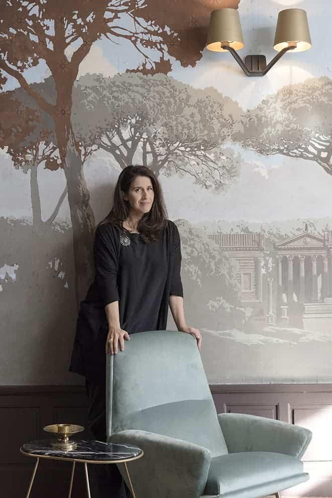 La styliste d'intérieur Nathalie Rives dans le Salon des Pins. Fauteuil vintage Guy Besnard (tissu Pierre Frey). Table Capsule (Nathalie Rives). Applique (Tom Dixon)