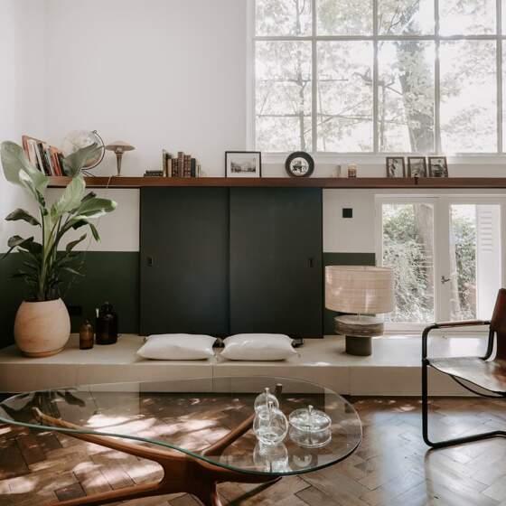 Les panneaux revêtus de tissu Kieffer-Rubelli coulissent pour caché la télévision ou la fenêtre menant au jardin. Lampe céramique de Rémi Fontaine