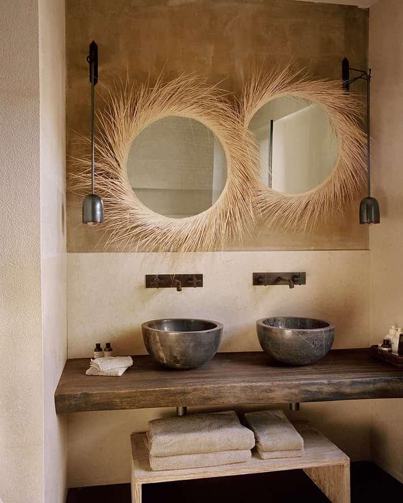 Salle de bains Chambre Master 1. Double vasque en granit poli. Plan de travail en chêne massif. Appliques en laiton vieilli. Miroirs en fibre de coco sauvage