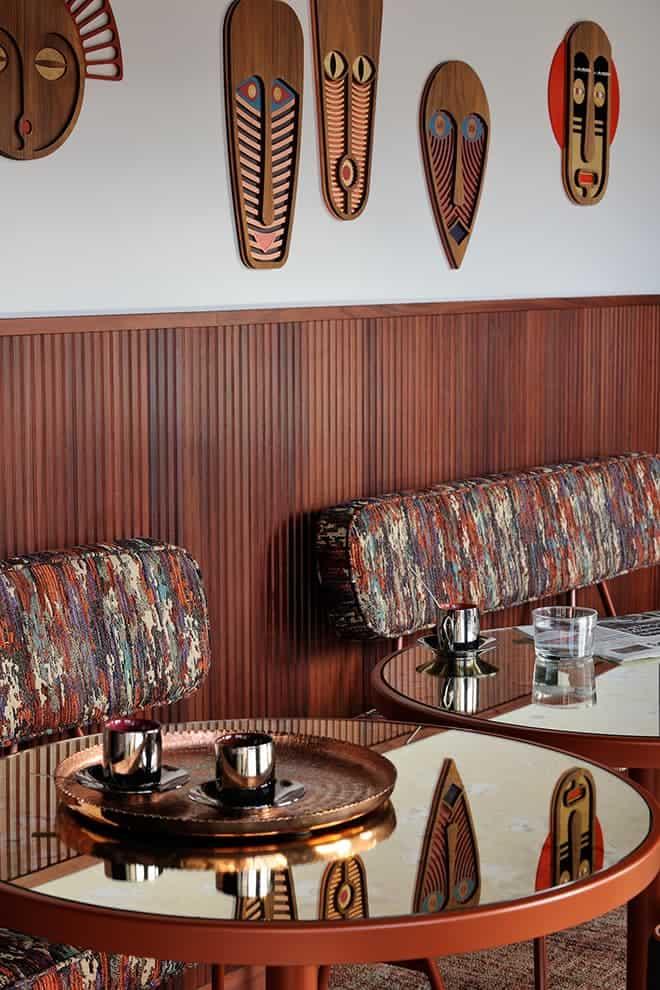 Adossées au pilier central, les banquettes en tissu Missoni Home et tables (Mambo Unlimited Ideas). Masques décoratifs (Umasqu)