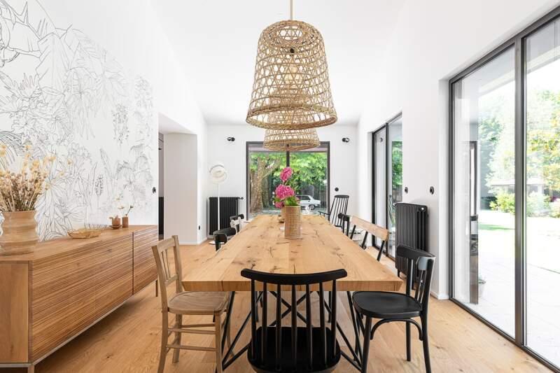 La salle à manger, située dans l'extension d'origine, récupère la hauteur sous plafond. Table dessinée par Régis Lannoy avec plateau en grumes de Venise. Suspensions Hyggelig. Papier peint Villa Nova