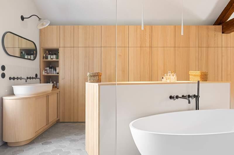 Rythmée par le panneautage vertical des rangements muraux, la salle de bains adoucit cette linéarité avec des éléments sanitaires tout en rondeur